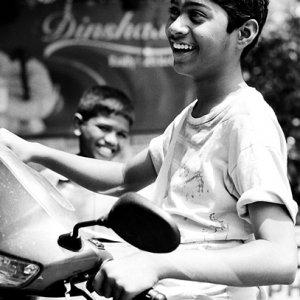 オートバイの上で笑う青年