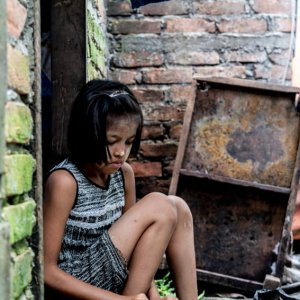 Girl cutting foodstuff with kitchen knife
