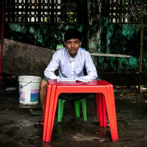 Schoolboy studying at red table