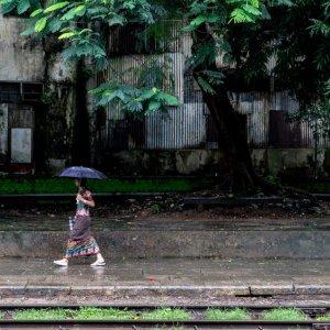 傘を差してプラットホームを歩く女性