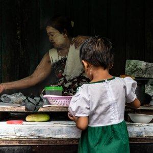 Little girl buying in delicatessen