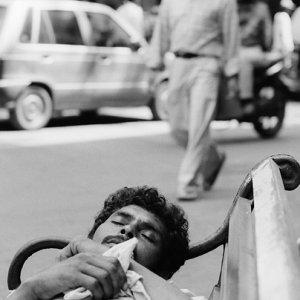 ベンチで寝る男