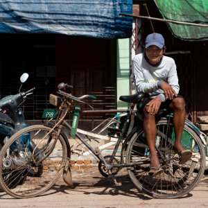 使い古された自転車タクシーの上で客待ちをする若い男