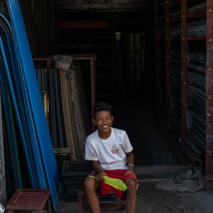 Boy sitting in storefront with a smile