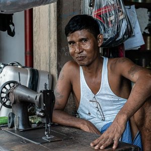 Man wearing tank top and sewing machine on table