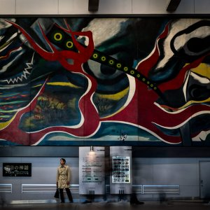 Man stopping under big wall painting by Taro Okamoto