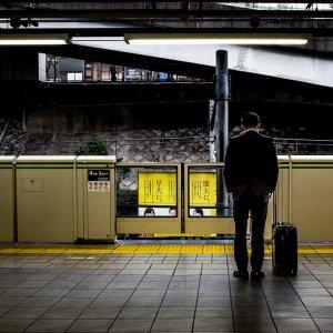 俯いて電車を待つサラリーマン