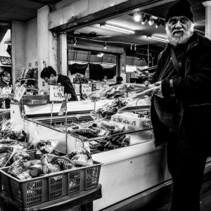 Man standing in front of vegetables in supermarket