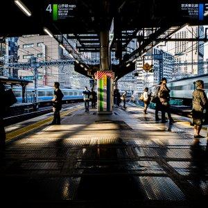 プラットホームの上で電車を待つ人たち