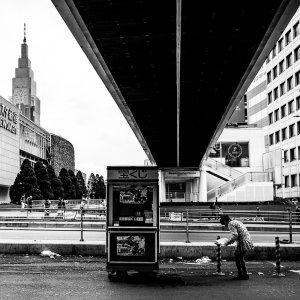 Woman cleaning up around hut under pedestrian bridge