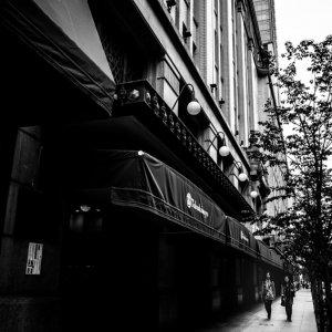 百貨店の前の歩道を歩く人影