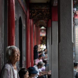 Older woman standing with beadrolls in her hands in Lungshan Temple