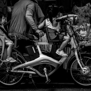 Two little girls riding on same bicycle in front of shop