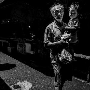 白蘭市場でおじいさんに抱かれて歩く幼い子供
