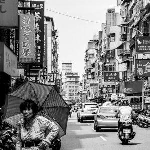 白蘭市場の近くを傘を差して歩いていた老婆