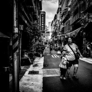 路地を歩く恰幅のいいお母さんと息子