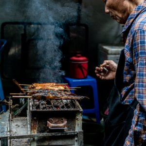 Man grilling fishes in Tha Tien Market