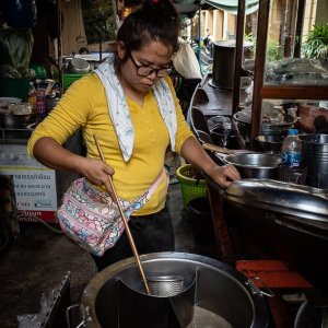 Woman boiling noodles in Tha Tien Market