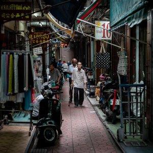 Old man walking dim lane in Chinatownr