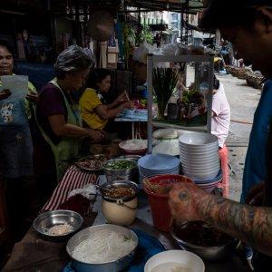 Tattoed man working in food stall