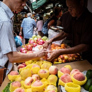 Man buying peach in a fruit shop