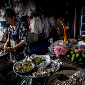 woman cutting bamboo sprouts in Maeklong Railway Market