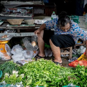 Older woman scouting around in Maeklong Railway Market