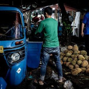 Men loading durians onto Bajaj