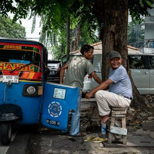 Blue three-wheeled taxi called Bajaj parked beside the tall street tree