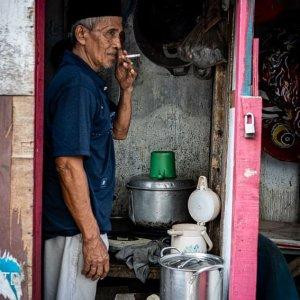 小屋の中で煙草を吸うソンコをかぶった男