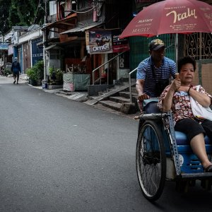 Pedicab called becak running in the residential area