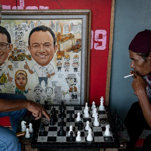 Men playing chess beside a paiting