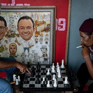 絵画の横でチェスに興じるふたりの男