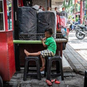 Boy watching the phone screen in Pasar Baru