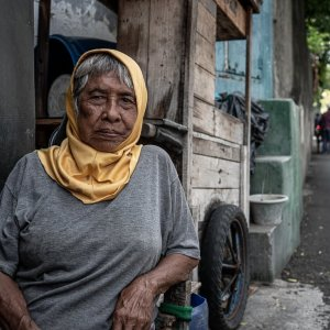 Older woman relaxing by the wayside in Jakarta