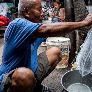 沢山のバケツを洗う老人