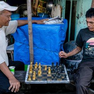 住宅街の町角でチェスをする男