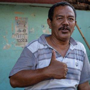 親指を立てたポロシャツの男