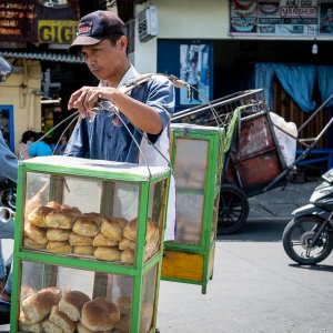 Young man peddling breads with a carrying pole