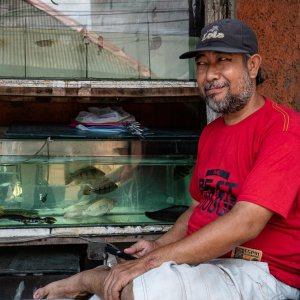 Man grinning in front of an aquarium