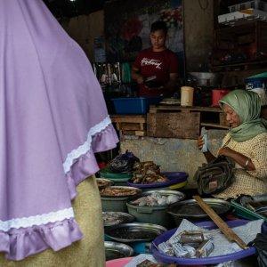 市場の魚屋で買い物する客