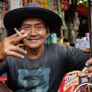 Becak driver in a hat smoking a cigarette