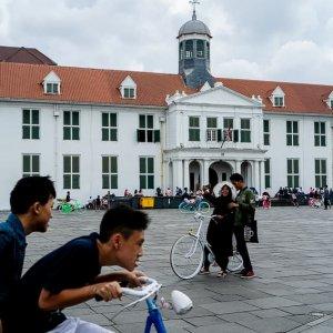 ファタヒラ広場を走る自転車と自撮りするカップル