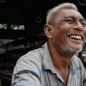 Man with gray hair laughing loudly