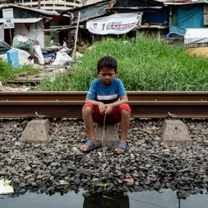 Boy sitting next to a puddle of water