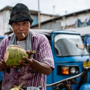 Coconut seller with a cigarette in his mouth