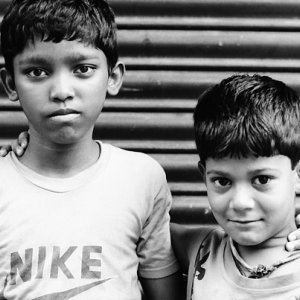 Two boys standing in front of shutter