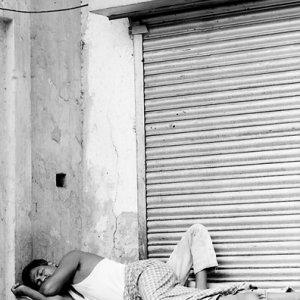 シャッターの前で寝る男
