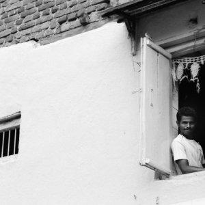 窓辺に立つ笑顔の男