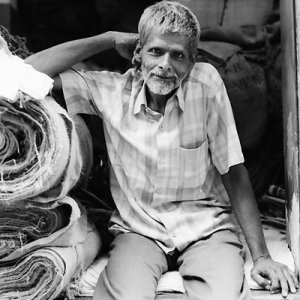 Man beside rolled textiles